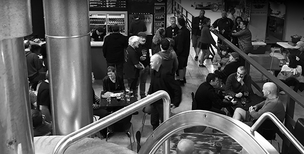 Busy taproom full of people drinking delicous beer